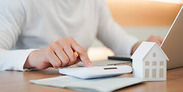 hand pressed on calculator to check and summary expense of home loan mortgage
