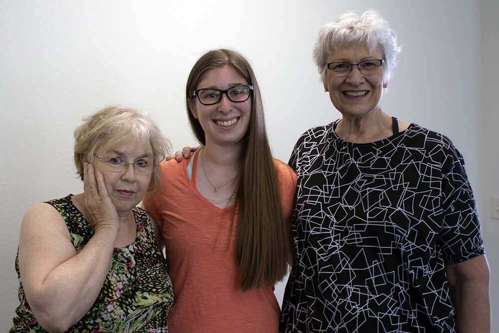 a young woman and two older women with arms around each other smiling