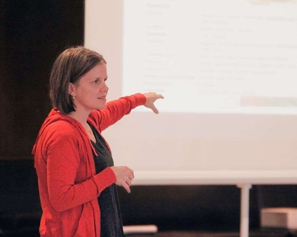 a woman pointing at a screen