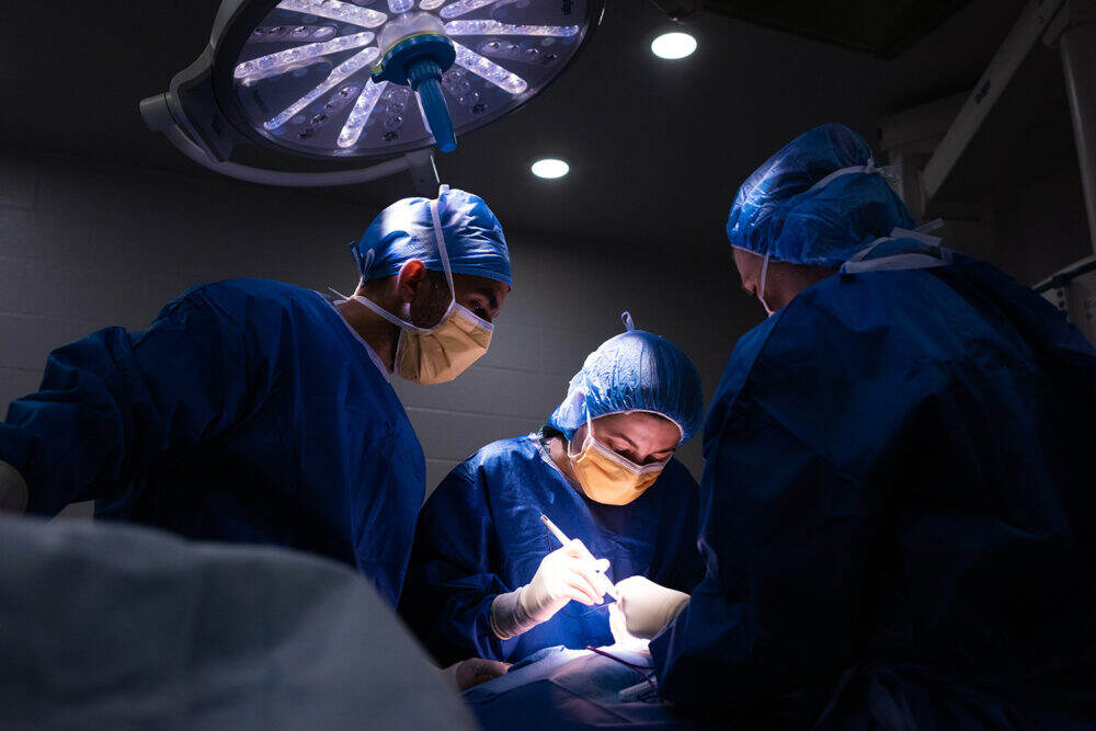 Three health care workers assist a surgery