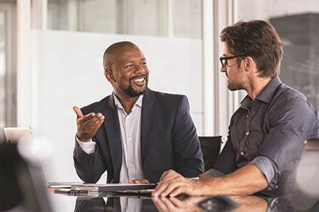 two male business owners sitting at a conference table talking