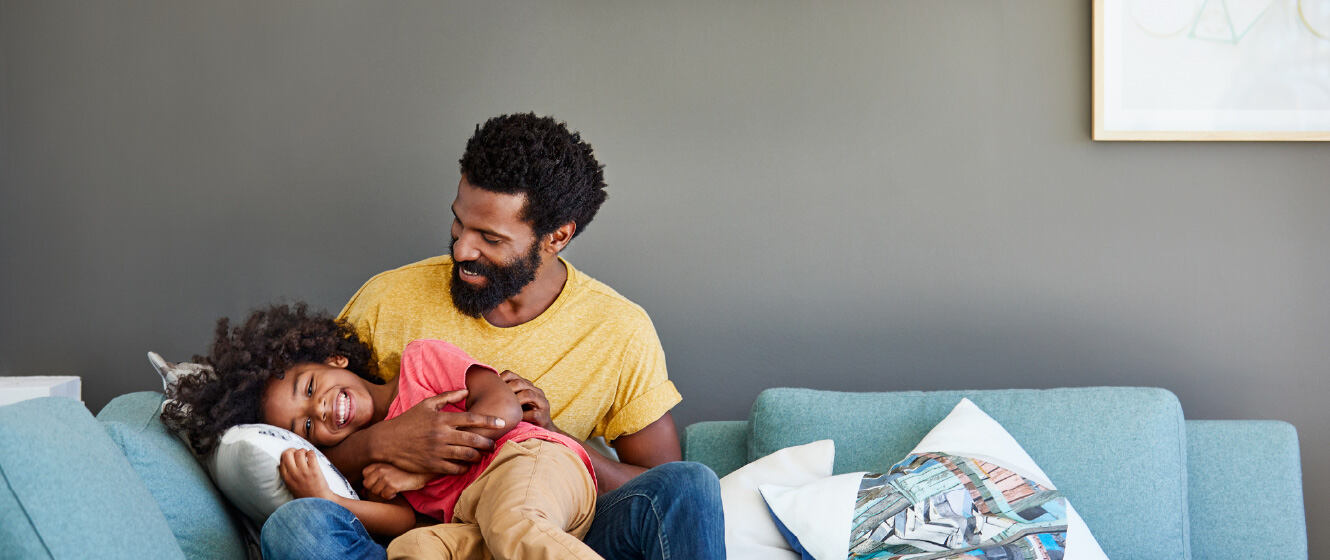 Man holding child on couch