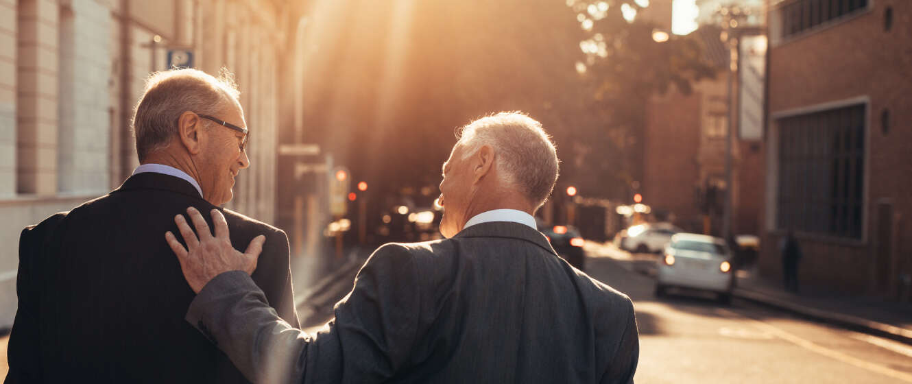 Two men in business suits walking outside together smiling