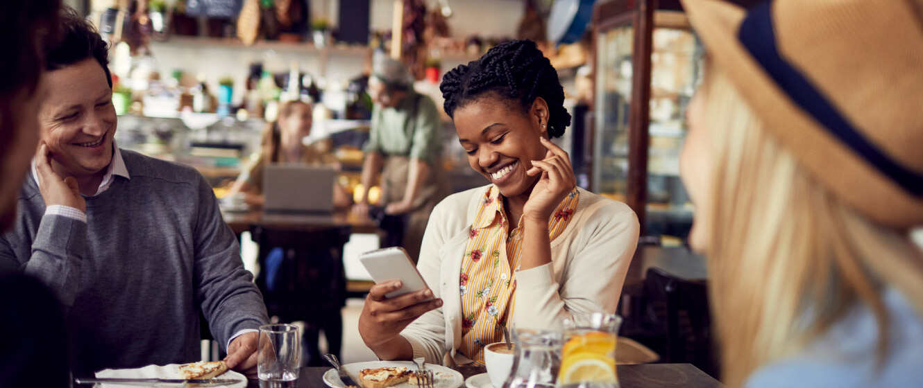 Woman sitting at table in restaurant with friends while smiling and looking at her smart phone