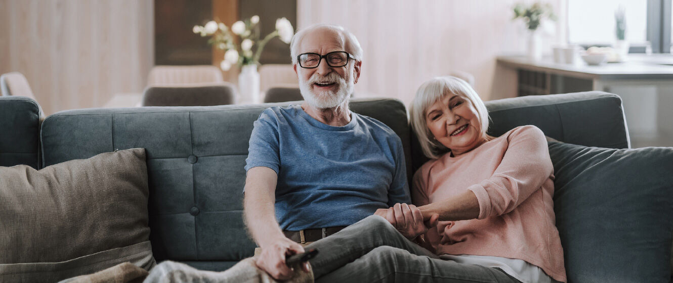 Two mature people sitting on couch together in their home while smiling