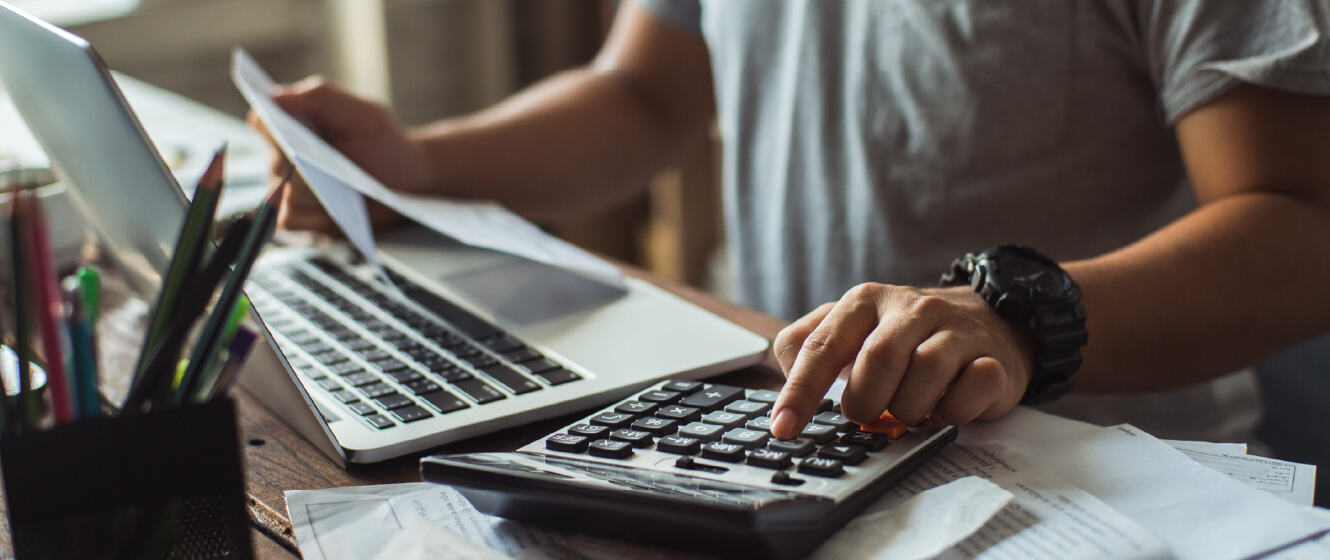 Person at desk with laptop open and working on calculator for bills
