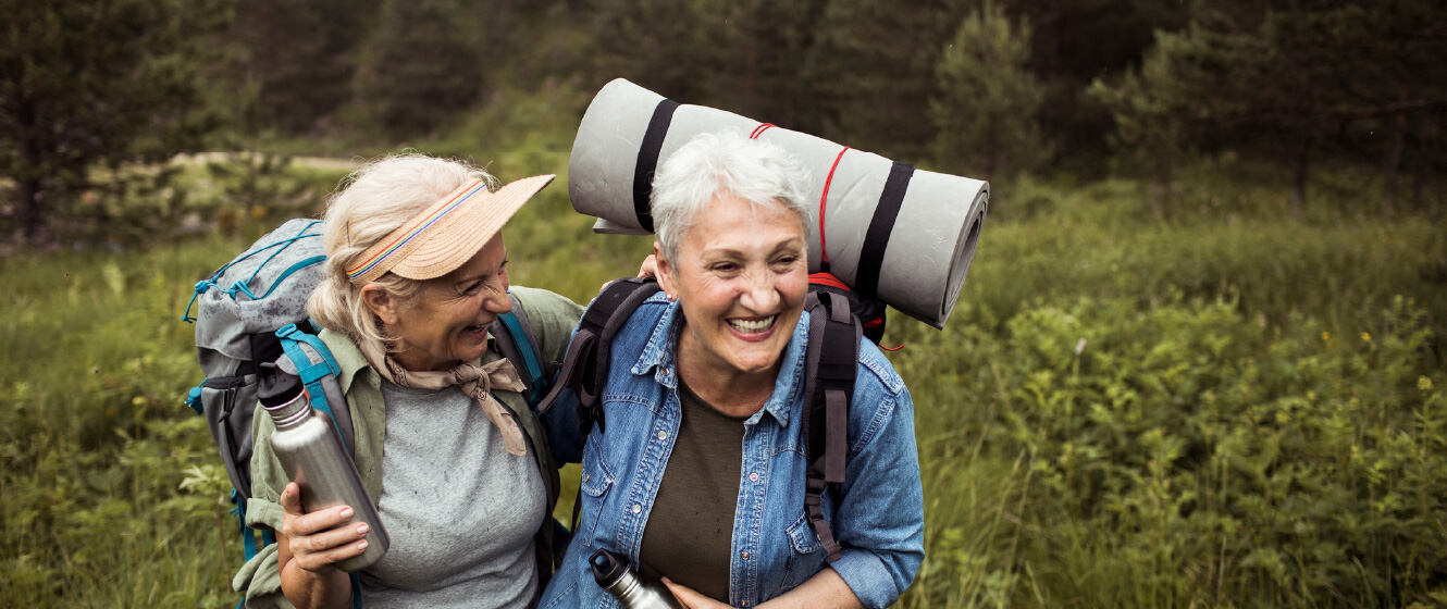 Two mature women hiking together and smiling