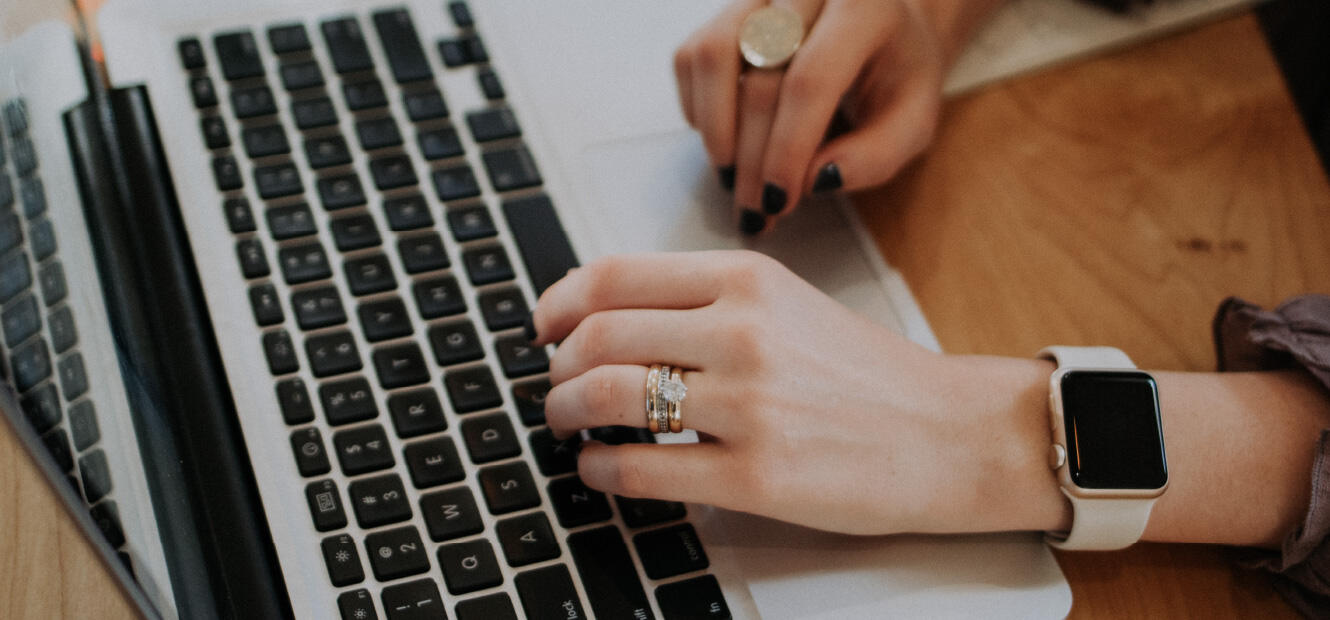 Close up of a person's hands while typing on their laptop