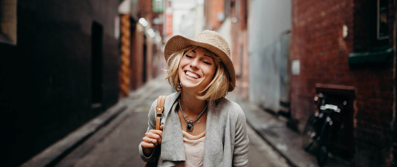 Woman smiling while walking down a city street
