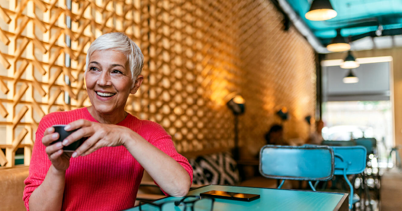 Mature woman sitting in restaurant alone and smiling