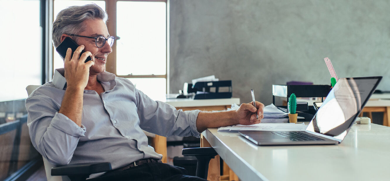 Man in office talking on the phone while sitting in front of his laptop