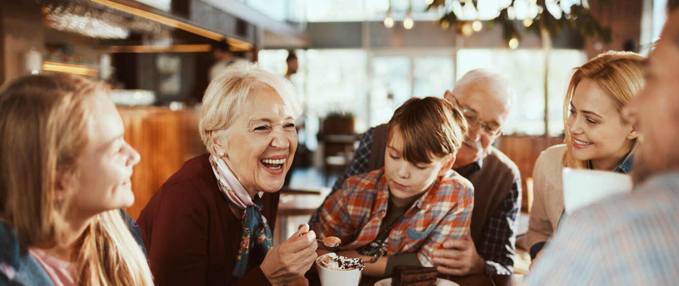 Multi generational family sitting around table in a restaurant eating dessert and laughing